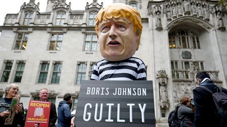 A man wearing a giant Boris Johnson mask, dressed as a prisoner, outside the Supreme Court in London