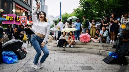 A dancer performs a k-pop routine for spectators on a street in the Hongdae district of Seoul. (Phot