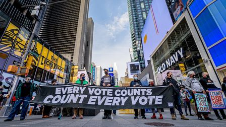 """Participants holding a banner reading: """"EVERY VOTE COUNTS/COUNT EVERY VOTE"""" at the protest in Times Square."""