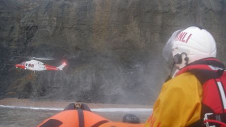 Lyme Regis lifeboat stands by as the coastguard helicopter rescues two people cut off by the tide ne