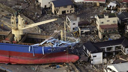 An under-construction boat (L) sits on land next to damaged homes in the city of Kamaishi in Iwate p