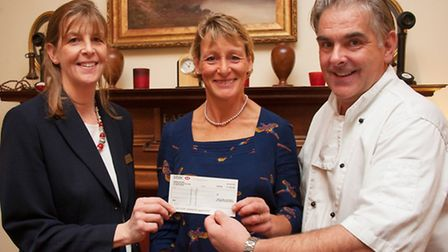 Mary King receives a cheque for the air ambulance from Carrie and Adam Southwell of the Fairwater H