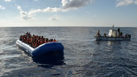 Migrants and refugees sit on a rubber boat as the Libyan coastguards patrol, during a rescue operati