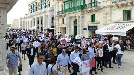 Journalists walk from the Parliament in Valletta, Malta, on October 19, 2017 in a silent commemorati