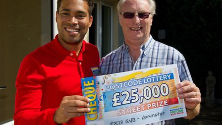 Danyl Johnson presents Edward Samwell with his 25.000 cheque at his home in Halletts Way Axminster.