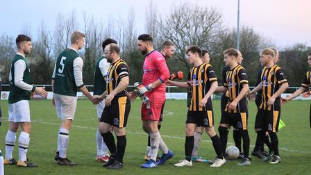 Axminster Town and University players shake hands before the start of their Tiger Way meeting that t