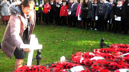 A pupil lays a cross at the war memorial during Axminster's Act of Remembrance. Picture Chris Carso