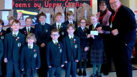 Chard School pupils present a cheque to Father Jeff. Picture Chard Scool