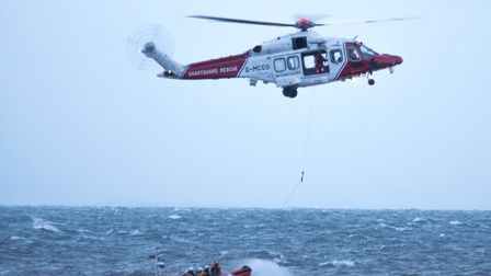 The coastguard rescue helicopter in action with a lifeboat in Lyme Bay. Picture: RNLI