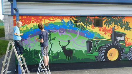 Youngsters work with a local artist to create the mural at Chulmleigh Youth Centre.