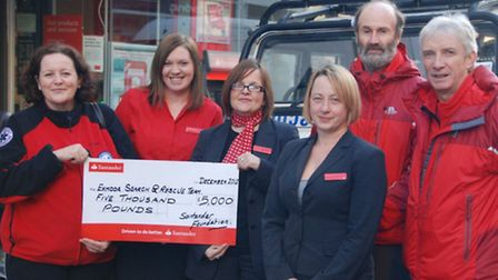 Sam Bryant-Jones, Exmoor Search and Rescue medical officer (far left), receives the cheque for 5,000
