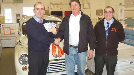 Competition winner Robert Allin (centre) receives his £500 prize money from MD Martin Harvey and Bed
