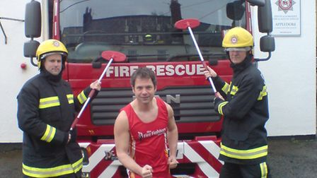Retained fire fighter Nick Williams (centre) gears up for his marathon with a charity car wash with