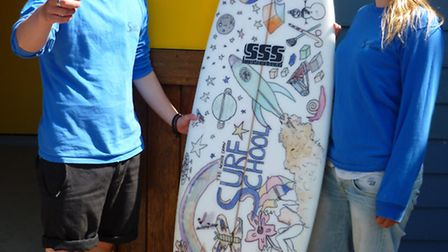 North Devon Surf School's Robert Marchant Greenslade and Laura Gregorczyk with the decorated board t