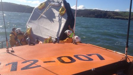 The all-weather lifeboat crew bring the lost life raft on to the deck of the Mersey class Spirit of