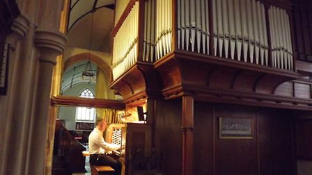 Holy Trinity organist Simon Helier at the console of the old church organ.