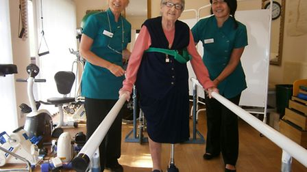 Battling back: Rita Newton pictured at Tyspane learning to walk again with assistance from staff Bab