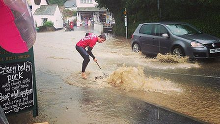 An instructor from Surfing Croyde Bay unblocking the drains in Hobbs Hill, Croyde this morning to av