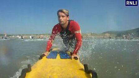 RNLI lifeguard James Bunney prepares to launch his board to rescue three people at Croyde beach on M