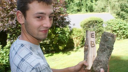 Matt Hunt is pictured with the log, which split to reveal a series of markings, thought to be the in