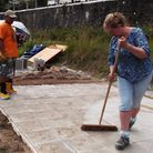 Morgan Quick, Steve Hughes and Steve Lewis lay paving slabs to provide a base for the on site timber