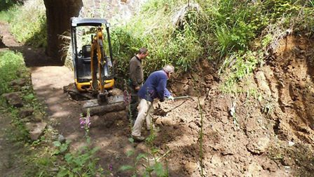 A volunteer and contractor uncover the canal wall at Beam.