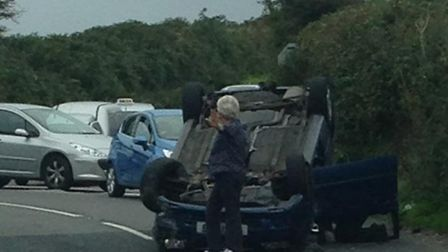 One passerby directs traffic while another talks to casualty Graham Boote after his car rolled at Tw