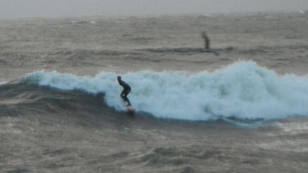 Surfers ride the storm surge at Lynmouth.