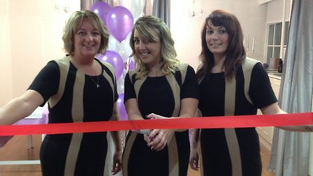 Owner Charley Klein cuts the red ribbon with Angels Marie Dunn (left) and Jeni Clarke.
