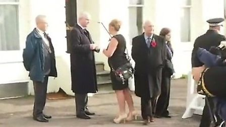 A still from the video showing Fiona Laign presenting Nick Harvey with the envelope at the parade on