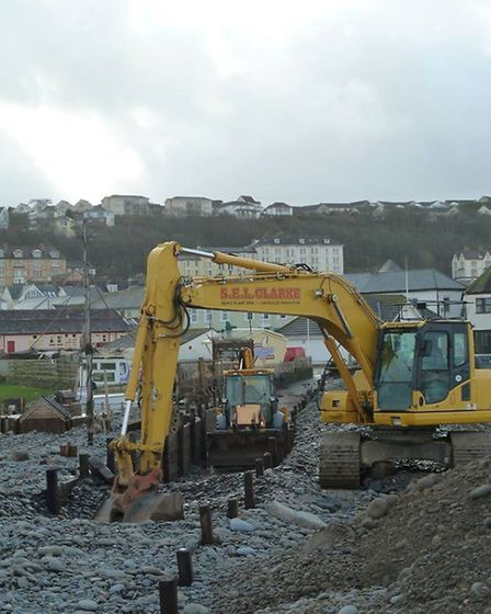 Preparing for the next tide: A digger attempts to reconstruct some of the Pebble Ridge before the ne