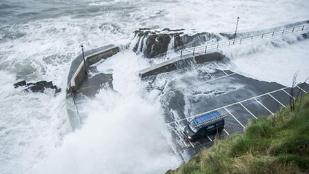 Van drivers are pictured risking their lives watching stormy seas behind the Landmark Theatre in Ilf