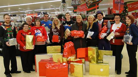 Barnstaple Sainsburys staff gather to present the mountain of toys to Claire Fisher of Encompass Sou