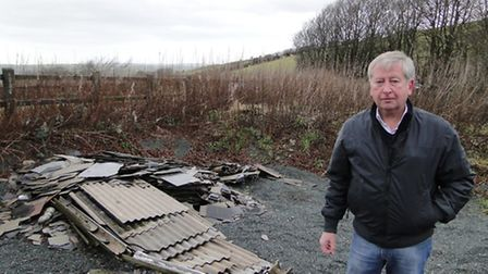 District Councillor Rodney Cann with the asbestos dumped at Breakneck Hole near Challacombe.