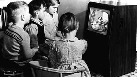 Children gather around a black and white television set watching children's show, Andy Pandy, first