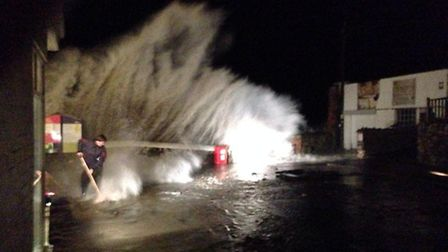 Residents attempt to unblock the drains as huge waves crash into Hele. Pic: Hele Mill.