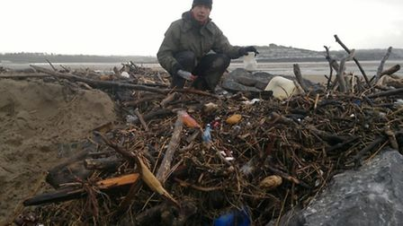 Mark French with some of the debris washed up at Crow Point during the recent storms.