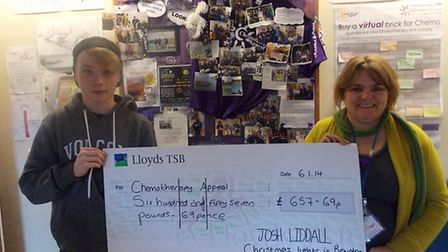Josh Liddall presents the proceeds of his Christmas lights collection to Julie Whitton.