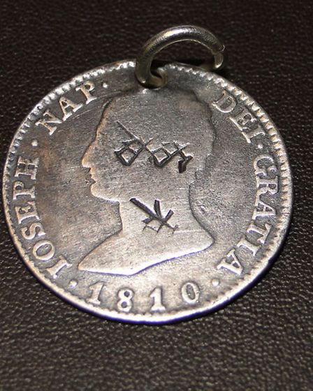 Do you know what these markings mean? Merlin is hoping to identify the symbols engraved on this coin