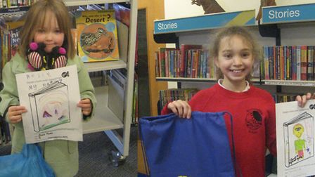 Rosie Ford, aged five, and Imogen Luke, nine, with their winning book covers and prizes.