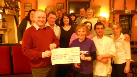 Staff and patrons at the Old Station Inn, Blackmoor Gate, join volunteer Christine Ward to present I