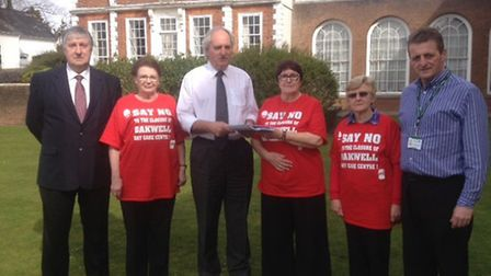 Devon County Council Leader John Hart (centre) is presented with the Oakwell day centre petition by