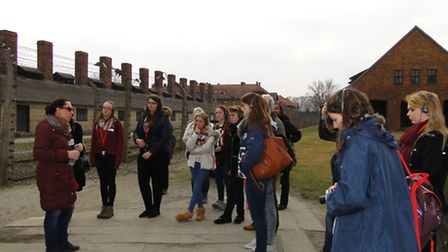 Students at the gates to Auschwitz One listening to the guide.