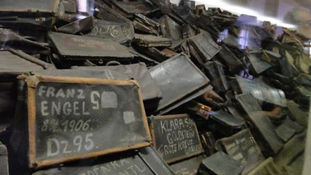 Suitcases with the names of their owners piled high in the Auschwitz Birkenau Museum.
