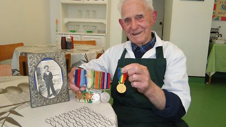 D-Day veteran Ernest 'Roy' Handford, pictured with his medals and a photograph of himself in 1940.