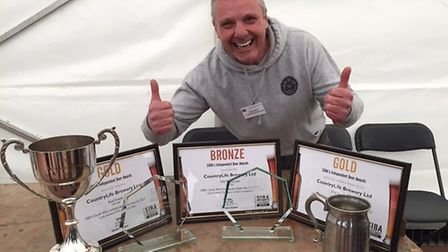 Simon Lacey of Country Life Brewery with the awards.