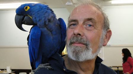 Dennis Crockford with Rio the magnificent hyacinth macaw. Picture: Tony Gussin