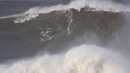 A screenshot from the video showing Andrew Cotton surfing a monster wave at the same spot in 2013.
