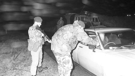 Members of the Ulster Defence Regiment search a car at a checkpoint while on patrol in County Down,