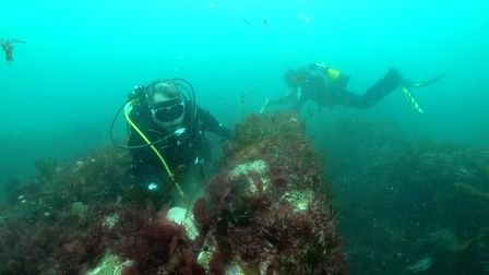 Two divers surveying what they believe is part of a gun casement on the wreck of HMS Montagu. Pictur